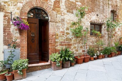 Adesivo As ruas calcetadas de as paredes decoradas com flores coloridas, Toscana, Itália