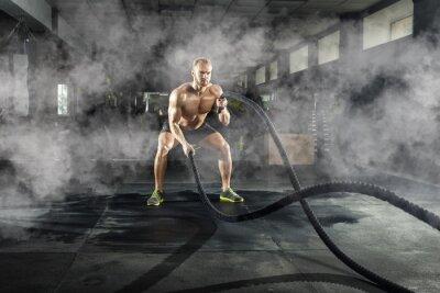 Adesivo Atlético jovem com corda de batalha fazendo exercício no ginásio de fitness. Conceito de esportes.