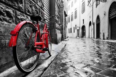 Adesivo Bicicleta vermelha do vintage retro na rua do cobblestone na cidade velha. Cor em preto e branco