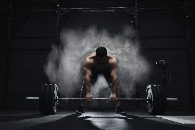 Adesivo Crossfit athlete preparing to lift heavy barbell in a cloud of dust at the gym. Barbell magnesia protection.