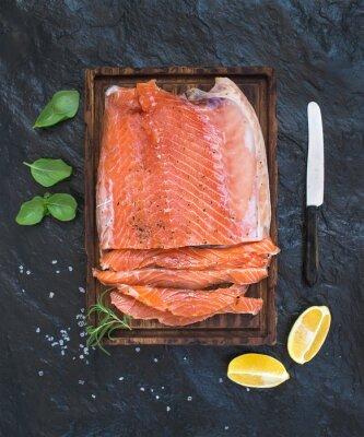 Adesivo Filete de salmão fumado com limão, ervas frescas e criados na placa de serviço de madeira sobre fundo de pedra escuro