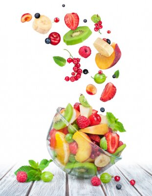 Adesivo fruit salad in glass bowl with ingredients in the air on white w