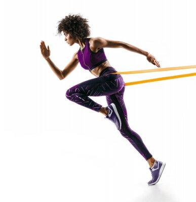 Adesivo Garota forte em silhueta usando uma banda de resistência. A foto da menina africana nova executa os exercícios da aptidão isolados no fundo branco. Vista lateral