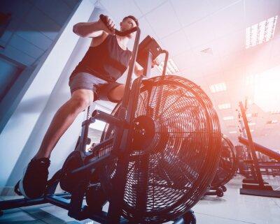 Adesivo Homens novos com corpo muscular usando a bicicleta do ar para o cardio- exercício no gym transversal do treinamento.