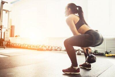 Adesivo Mulher atlética que exercita com o sino da chaleira ao estar na posição de agachamento. Mulher muscular que faz o exercício do crossfit na ginástica.