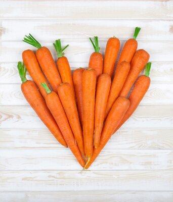 Adesivo o coração da cenoura em um fundo madeira
