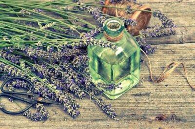 Adesivo Óleo de lavanda erval com flores frescas no fundo de madeira