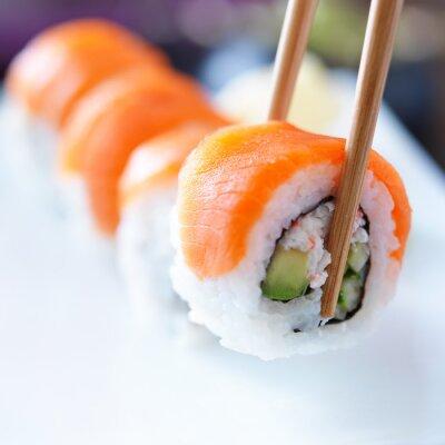 Adesivo pegando um pedaço de sushi com pauzinhos