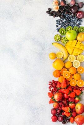 Adesivo Rainbow fruits berries background on white. Top view of strawberries blueberries cherries mango apple lemons oranges red currants plums blackberries, selective focus