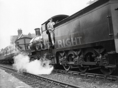 Adesivo Sheffield Park, England - circa 1972 - A steam locomotive pulls a passenger train into Sheffield Park station on the preserved Bluebell Line Railway.