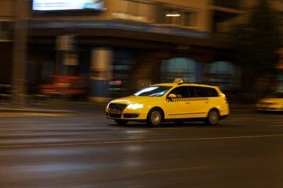 Adesivo táxi amarelo move na rua da cidade à noite