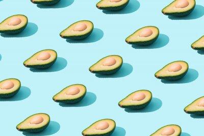 Adesivo Trendy sunlight Summer pattern made with avocado fruit on bright light blue background. Minimal summer concept.