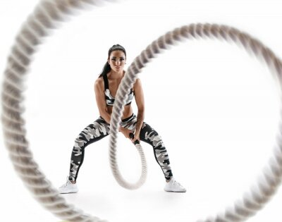 Adesivo Woman doing exercises with battle rope. Photo of muscular model in military sportswear isolated on white background. Strength and motivation