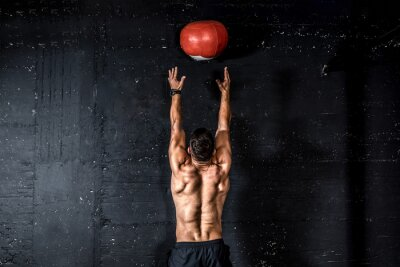Adesivo Young strong sweaty focused fit muscular man with big muscles doing throwing medicine ball up on the wall for training hard core workout in the gym real people selective focus