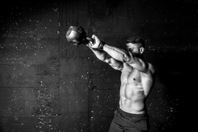 Adesivo Young strong sweaty focused fit muscular man with big muscles holding heavy kettle bell for swing cross training hard core workout in the gym black and white