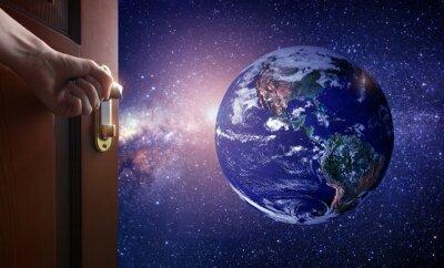 Fotomural A mão abre a porta vazia do quarto à terra do planeta do espaço. Alguns
