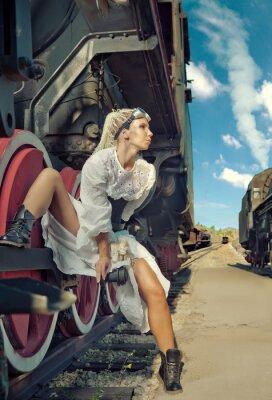 Fotomural A mulher no vestido do vintage está sentando-se na roda da locomotiva.