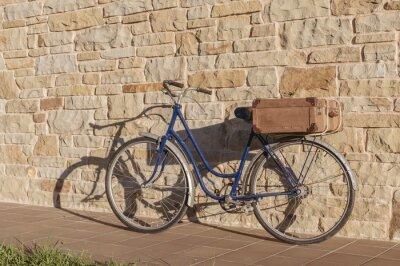Fotomural Bicicleta do vintage e mala de viagem velha em um muro de pedra