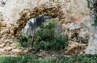 Fotomural Buraco na parede do edifício de pedra abandonada.