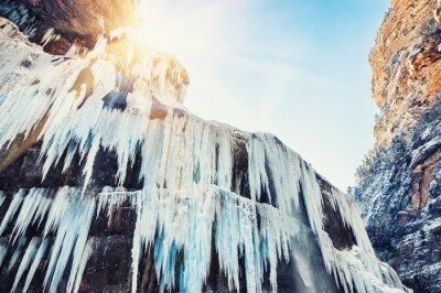 Fotomural Cachoeira congelada nas montanhas no por do sol.