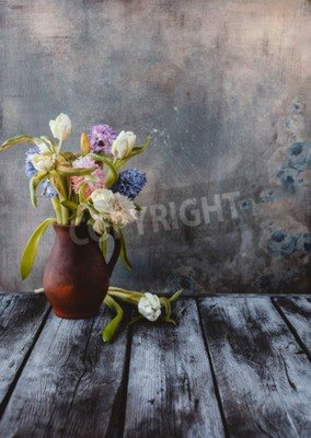 Fotomural Ceramic jug with spring flowers on wooden table