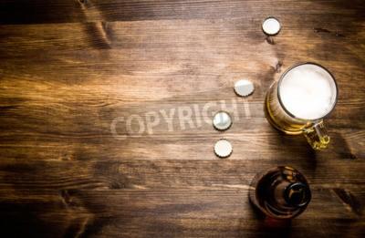 Fotomural Cerveja estilo garrafa, cerveja no vidro e cobre na mesa de madeira.