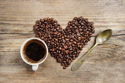 Fotomural Chávena de café e coração feito de grãos de café na tabela de madeira. Para