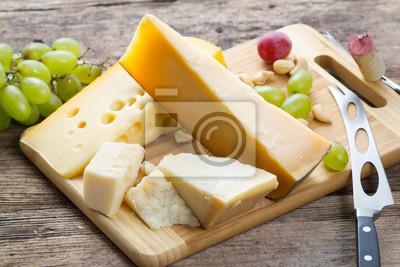 Fotomural Conjunto de vários queijos com uva sobre fundo de madeira