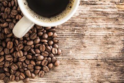 Fotomural Copo de café e feijão em uma mesa de madeira