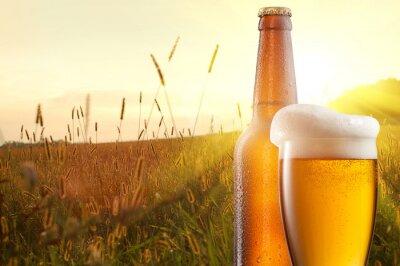 Fotomural Copo de cerveja e uma garrafa de encontro ao campo de trigo e pôr do sol