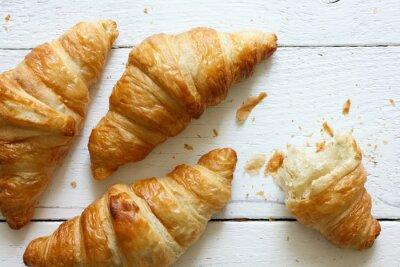 Fotomural Croissants dourados no branco madeira rústica, de cima.