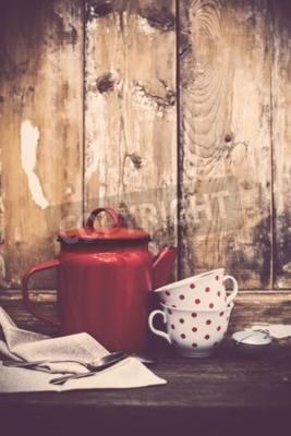 Fotomural Decoração de cozinha vintage, pote de café em esmalte vermelho e copos com bolinhas em um fundo antigo de placa de madeira com espaço de cópia. Decoração rústica da casa.