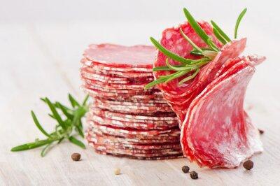 Fotomural Descrição da foto: Fatias de salsicha do salami em uma tabela de madeira.