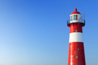 Fotomural Farol vermelho e branco e um céu azul claro