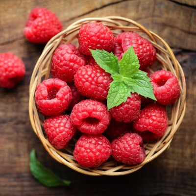 Fotomural Fresh ripe red raspberries in a wicjer bowl on dark rustic wooden background