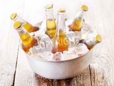 Fotomural Garrafas de cerveja fria em balde com gelo na mesa de madeira