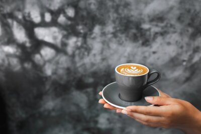 Fotomural Gray cup of fresh cappuccino in woman hands on background of gray concrete cement textured wall. Trendy hipster cafe design.