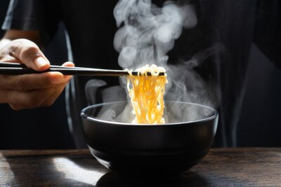 Fotomural Hand uses chopsticks to pickup tasty noodles with steam and smoke in bowl on wooden background, selective focus. Asian meal on a table, hot food and junk food concept
