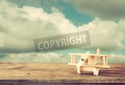 Fotomural Imagem do avião de brinquedo de madeira sobre a mesa de madeira contra o céu nublado. Imagem de estilo retro