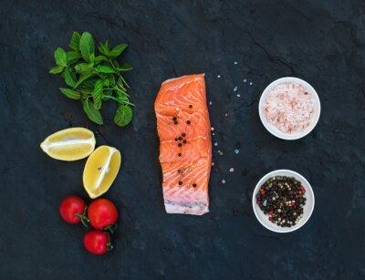 Fotomural Ingredientes. Raw salmão filé, limão, tomate cereja, hortelã fresca e especiarias sobre fundo de pedra escura