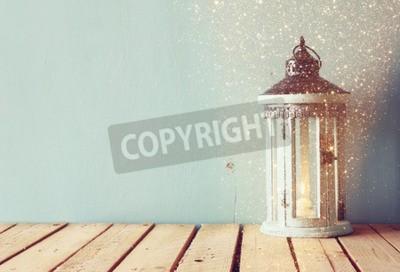 Fotomural Lanterna de madeira branca do vintage com vela ardente e filiais de árvore na tabela de madeira. Imagem filtrada retro com superposição do brilho