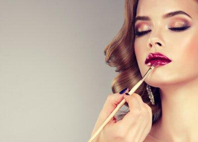 Fotomural Mão do maquiador da composição, bordos da pintura do modelo bonito novo. Maquiagem em andamento.