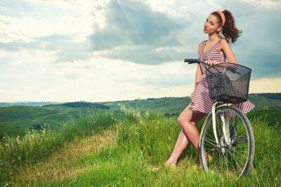 Fotomural Menina bonita com bicicleta vintage ao ar livre, Toscana tempo de verão