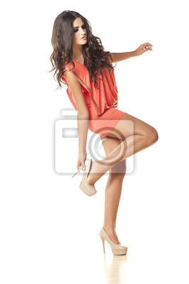 8bc5661ed Fotomural Menina bonita no vestido laranja colocando em seus sapatos de  salto alto