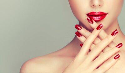 Fotomural Menina bonita que mostra pregos vermelhos do manicure. Maquiagem e cosméticos