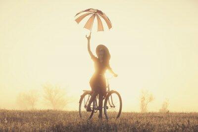 Fotomural Menina com guarda-chuva em uma bicicleta no campo no tempo do nascer do sol