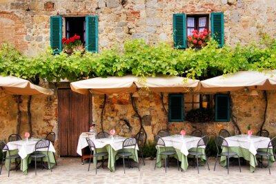 Fotomural Mesas de café e cadeiras fora de um edifício de pedra na Toscana