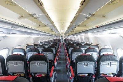 Fotomural Modern interior of aircraft. Black and red seats inside airplane. Symmetric vanishing row of seats inside air transport. Economy class of flight. Equipment for travelling. Empty illuminated plane.