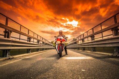 Fotomural Moto da strada pronta alla partenza sotto un cielo rosso al tramonto