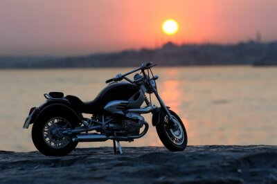 Fotomural Motorcycle on the rocks in sunset and golden hours